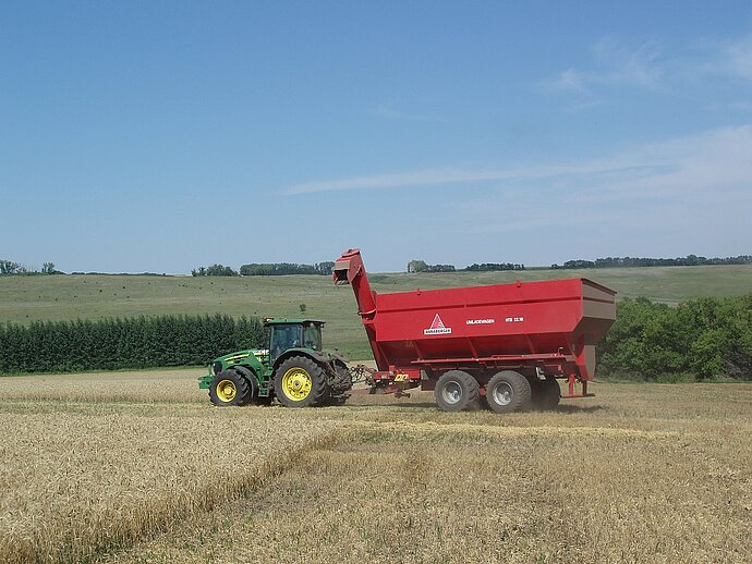 Photo of Trakor and Combine harvester harvesting a grain field