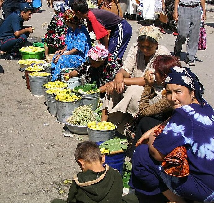 Photo of women in traditional costume selling their agricultural produce at a market in Uzbekistan